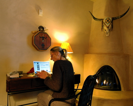Blogging from Taos: Linda at the computer in our cozy room in Taos