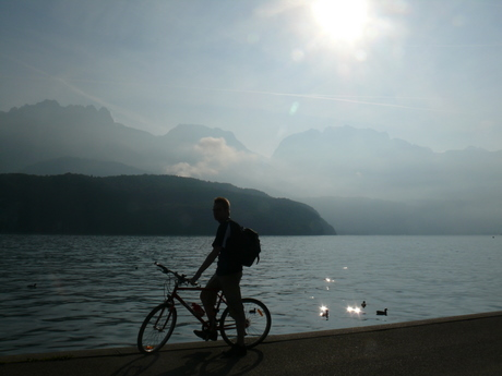 A bicyclist pauses on the western shore ('Rive Gauche') of Lac d'Annecy